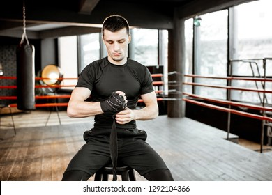 Portrait of a young athletic man winding bandage on the wrists, preparing for training on the boxing ring at the gym