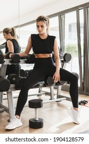 Portrait of young athletic woman sitting on dumbbell rack in gym