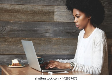 Portrait of young attractive African female blogger, typing a new challenging post during lunchtime at a cafe, with laptop and smart phone with copy space for your promotional content on the table