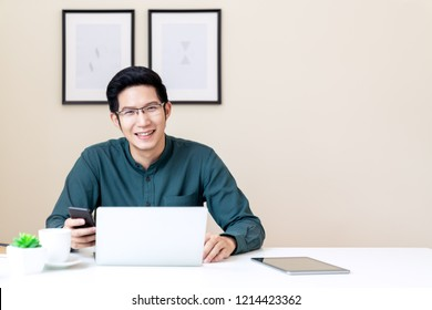 Portrait of young attractive asian businessman or student using mobile phone, laptop, tablet, drinking coffee sitting on desk table wearing green shirt look at camera in home office with copy space.