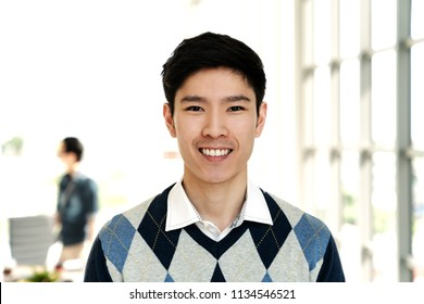 Portrait of young attractive asian creative man smiling and looking at camera in modern office feeling confident and positive. Headshot of chinese male employee, entrepreneur or college student.