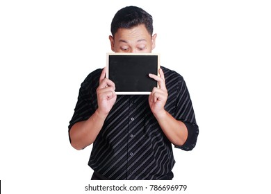 Portrait of young attractive Asian man wearing black shirt, holding and showing small empty copy space blackboard covering his face, isolated on white