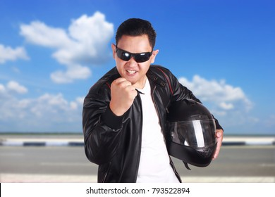 Portrait of young attractive Asian men wearing black leather jacket and sunglasses showing cynical unhappy angry facial expression putting up his fist challenge to fight