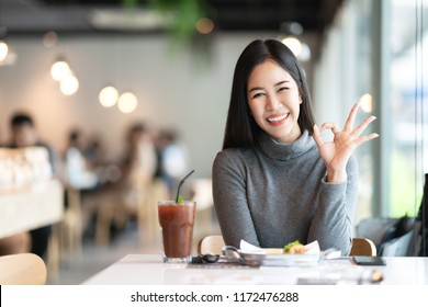 Portrait of young attractive asian woman looking at camera smiling with urban lifestyle concept at blurred cafe background with bokeh. Headshot of cute girl gesture hand okay sign feeling positive.