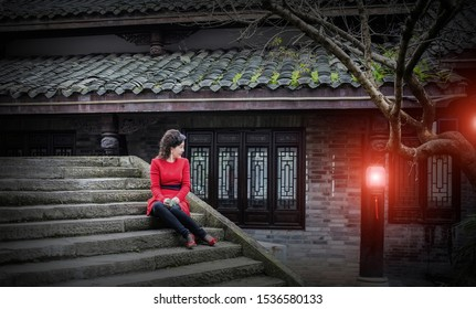 A portrait of a young, attractive Asian woman sitting on the steps.She was wearing a red autumn dress and looked at the red lanterns hanging from the eaves