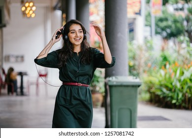 Portrait of a young, attractive and beautiful Indian Asian millennial girl dancing as she listens to music on her headphones. She is streaming music on her smartphone and is enjoying it as she dances.