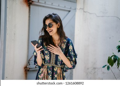 Portrait of a young, attractive and beautiful Indian Asian woman wearing a dress and sunglasses with her smartphone. She looks surprised and delighted and is smiling as she looks at her phone.