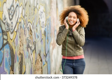 Portrait of young attractive black girl in urban background listening to the music with headphones. Woman wearing leather jacket and blue jeans with afro hairstyle