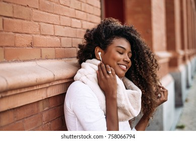 Portrait of young attractive black girl in urban background listening to the music with headphones.