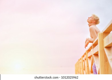 Portrait of young attractive blonde woman with closed eyes enjoying the fresh sea air on the wooden deck on the beach.