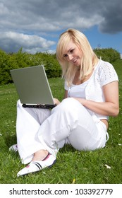 Portrait of a young attractive blonde woman with a laptop outside