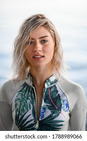 portrait of young attractive blonde woman with wet hair in gray wetsuit on blurred water background