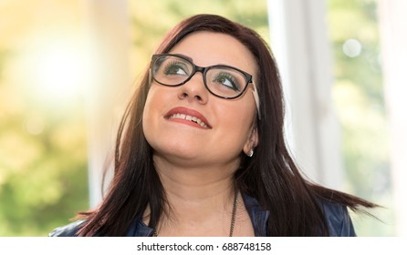 Portrait of young attractive brunette looking up, light effect