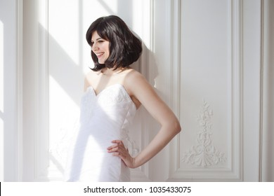 Portrait of young attractive brunette with short hair in a wedding dress. She is standing at the white walls.