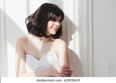 Portrait of young attractive brunette with short hair in a wedding dress. She is standing at the white walls, free space on the right. Joyful bride.