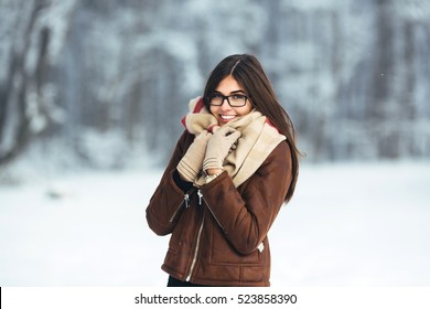 portrait of young attractive brunette with sunglasses in winter park