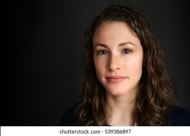Portrait of young attractive brunette woman with black backdrop
