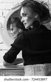 Portrait of young attractive brunette woman with glamorous makeup and wearing black deep-necked blouse, posing near the mirror in black and white