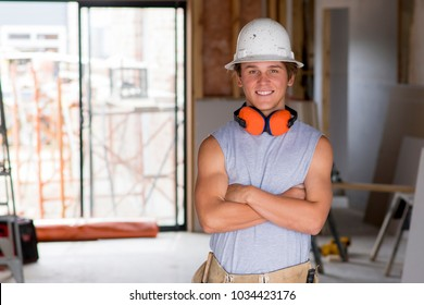 portrait of young attractive builder man on his 20s posing happy confident and proud at construction site wearing protection helmet in renovation industry blue collar work concept