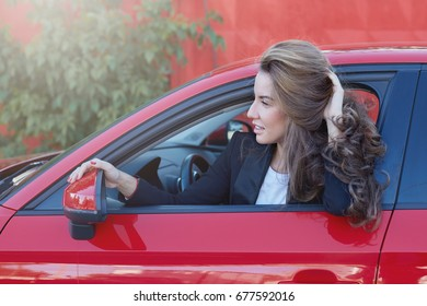 Portrait of young attractive Caucasian business lady with long hair wearing formal suit on the wheel of red modern car looking for somebody, waiting for colleage to come to the office together.