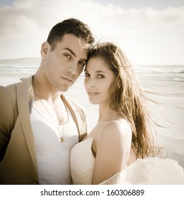 Portrait of young attractive caucasian couple on beach at sunrise