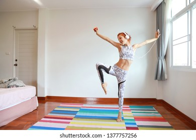 portrait of young attractive caucasian woman in black and white sportswear who listening and dancing music from cell phone and headphone while holding apple  in bedroom with happy and smiling face