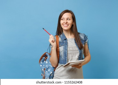 Portrait of young attractive cheerful woman student in denim clothes with backpack hold notebook pointing pencil aside isolated on blue background. Education in high school university college concept