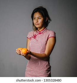 Portrait of a young and attractive Chinese Asian teenage girl in a traditional Chinese dress (qipao) smiling as she offers a pair of Mandarins to signify wealth to the host that she is visiting.