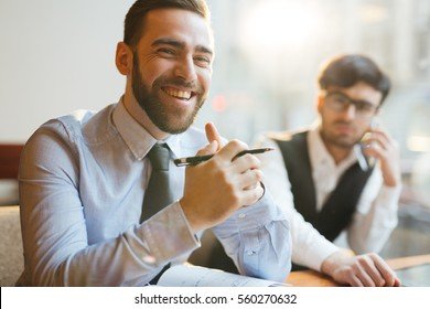 Portrait of young attractive company executive sitting at table with clasped hands, holding pen and smiling at camera cheerfully, sitting next to his pensive assistant.