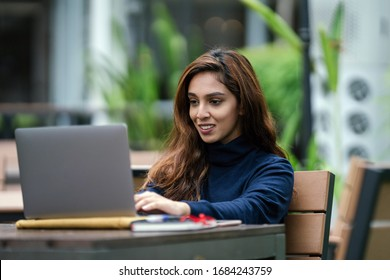 Portrait of a young, attractive, confident, smart and studious Indian Asian smiling as she types and works on her laptop computer. She is sitting at a desk in her university, office or coworking space