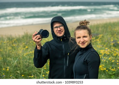Portrait of young and attractive couple in love close up looking at camera and smiling. Green grass and beach on background, Norway. Soft focus.
