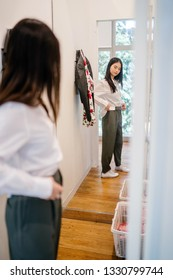 Portrait of a young, attractive and cute Chinese Asian girl trying out clothes in a fitting room. She is shopping for new clothes and is trying out a casual business outfit in front of a mirror.