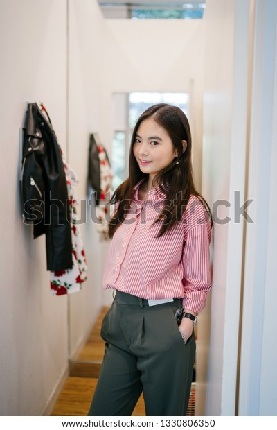 e44062a40 Portrait of a young, attractive and cute Chinese Asian girl trying out  clothes in a