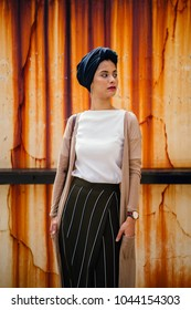 A portrait of a young, attractive, elegant Muslim (Asian) woman standing against a vintage, retro and stained wall. She is wearing a blue turban (hijab, headscarf) and is fashionable and elegant.