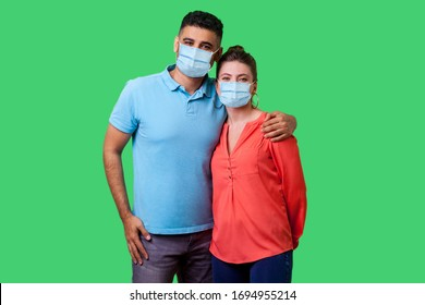 Portrait of young attractive family couple with surgical medical mask standing together, embracing and looking at camera with smile, strong relations. isolated on green background, indoor studio shot