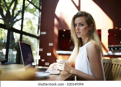 Portrait of a young attractive female creative designer sitting with laptop computer in modern cafe interior, beautiful woman freelancer using net-book. Infographics elements of email envelope sings
