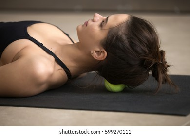 Portrait of young attractive female practicing self-massage technique applying tennis balls for headache relieving, working out, closeup, grey floor studio background