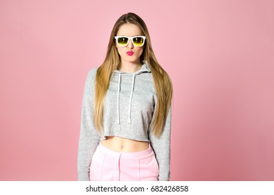 Portrait of young attractive funny teenager girl with shrtaight blonde hair and sunglasses in trendy clothes on the pink background, studio shooting, displeasure and complain emotion