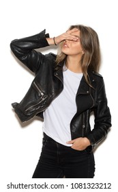 Portrait of young attractive girl in a black leather jacket smiling and cover her mouth with a hand