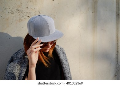 Portrait of a young attractive girl with cap. Female model wearing a gray blank cap and sunglasses looking away.