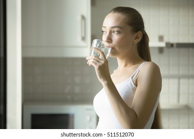 Portrait of a young attractive girl drinking water in the kitchen. Health care concept photo, lifestyle
