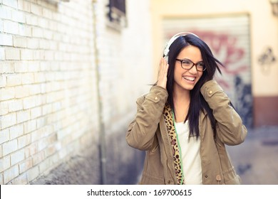 Portrait of young attractive girl in urban background listening to music with headphones