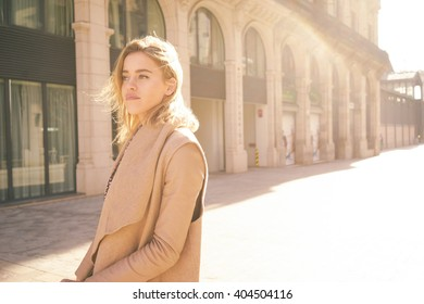 Portrait of a young attractive girl who looking for a hotel that is booked online.young attractive blonde girl arrived in a European city to spend a weekend and enjoying the spring sunshine