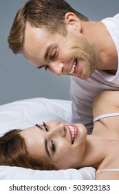Portrait of young attractive happy couple hugging on the bed at bedroom. Caucasian models in love, relationship, dating, happy people, bedtime concept shot.