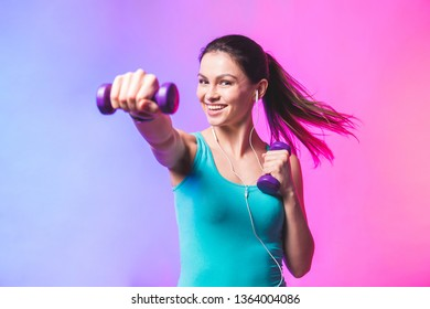 Portrait of young attractive happy woman in sport clothes with beautiful smile holding weight dumbbell doing fitness workout isolated on white background in healthy lifestyle concept.
