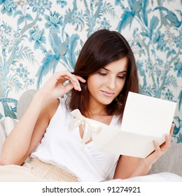 Portrait of young attractive happy woman, reading valentine card while sitting on comfortable sofa at living room at her home