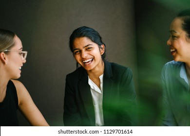 Portrait of a young and attractive Indian Asian business woman having a discussion with her diverse team (a Chinese and a Caucasian woman). She is wearing a professional suit and smiling.