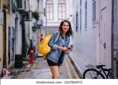Portrait of a young and attractive Indian Asian woman in a denim jacket and yellow backpack enjoying music on her headphones. She is smiling as dancing as she walks down an alley on her way somewhere.