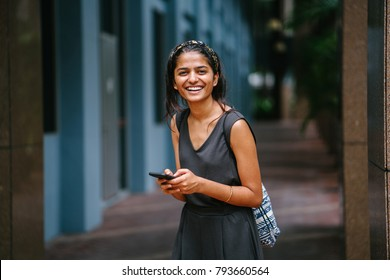 Portrait of young and attractive Indian Asian woman standing in the sun against a dark background in the city. She's standing and smiling in the daytime with her smartphone in hand.