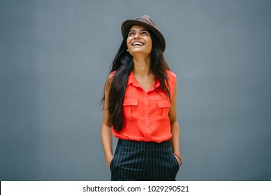 Portrait of a young attractive Indian woman standing outdoors against a blue grey background and looking up with her hands in her pockets. She is dressed fashionably with a hat and looks happy.